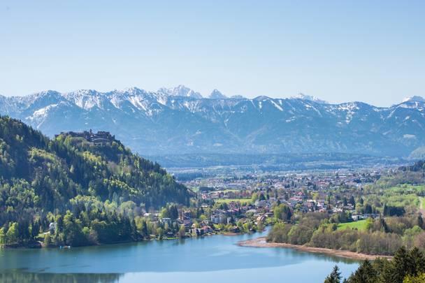 <p>Blick über den sonnigen und frühlingshaften Ossiacher See in Richtung der Draustadt Villach mit der Burg Landskron auf der linken Seite und den Karawanken im Hintergrund. Im hellblauen Himmel leuchten die schneebedeckten Bergspitzten der südlichen Karawanken. Das Wasser des Ossiacher Sees, dem drittgrößen See Kärntens, schimmert blau und die Landschaft von hellgrün bis dunkelgrün. Die Burg Landskron beheimatet auch eine Adlerarena mit einem in Europa einzigartigem Greifvogelpark.</p>
