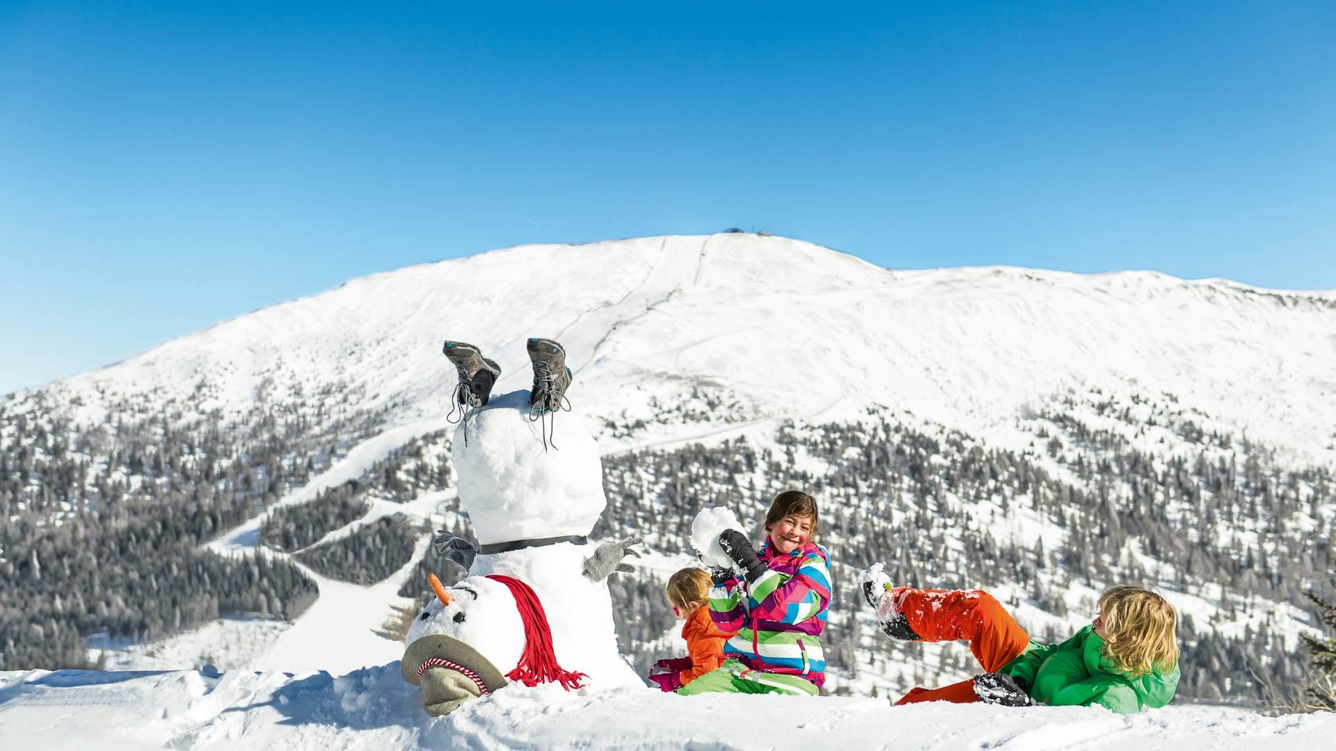 Katschberg_Kinder haben Spaß im Schnee mit Schneemann